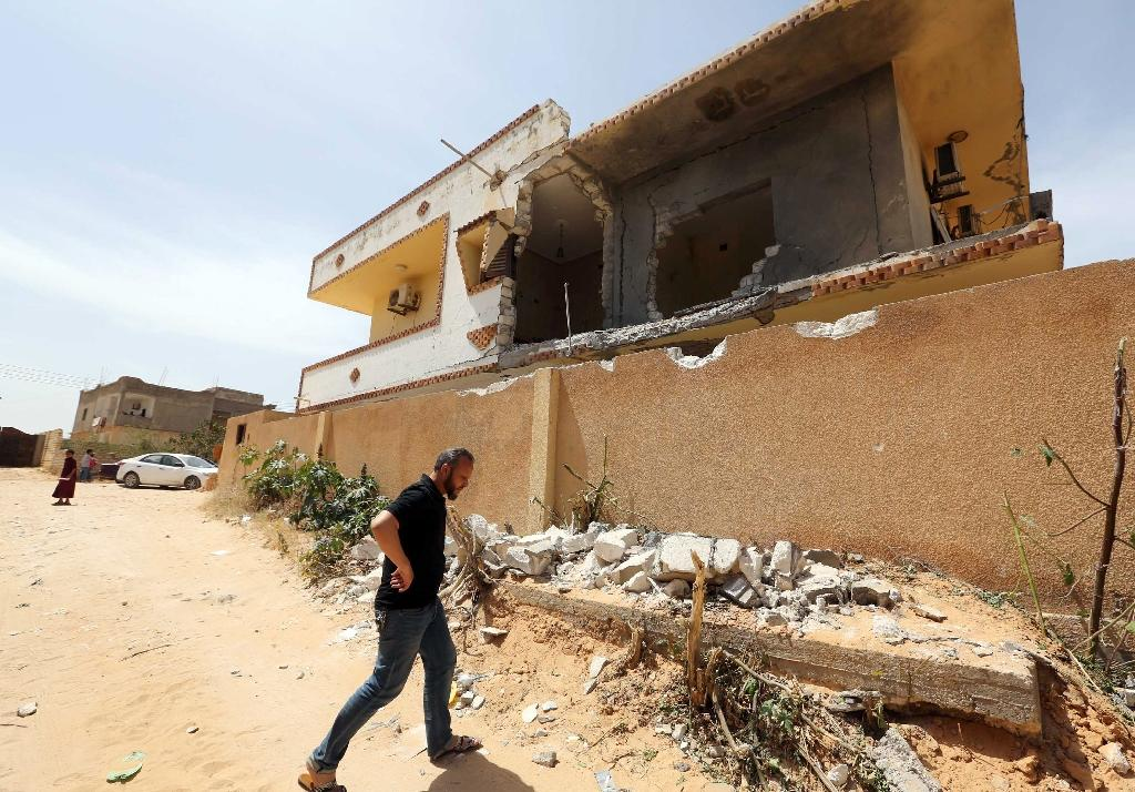 A man walks past a damaged house on May 6, 2015 in the coastal town of Zawiya after the house was reportedly hit by a rocket (AFP Photo/Mahmud Turkia)