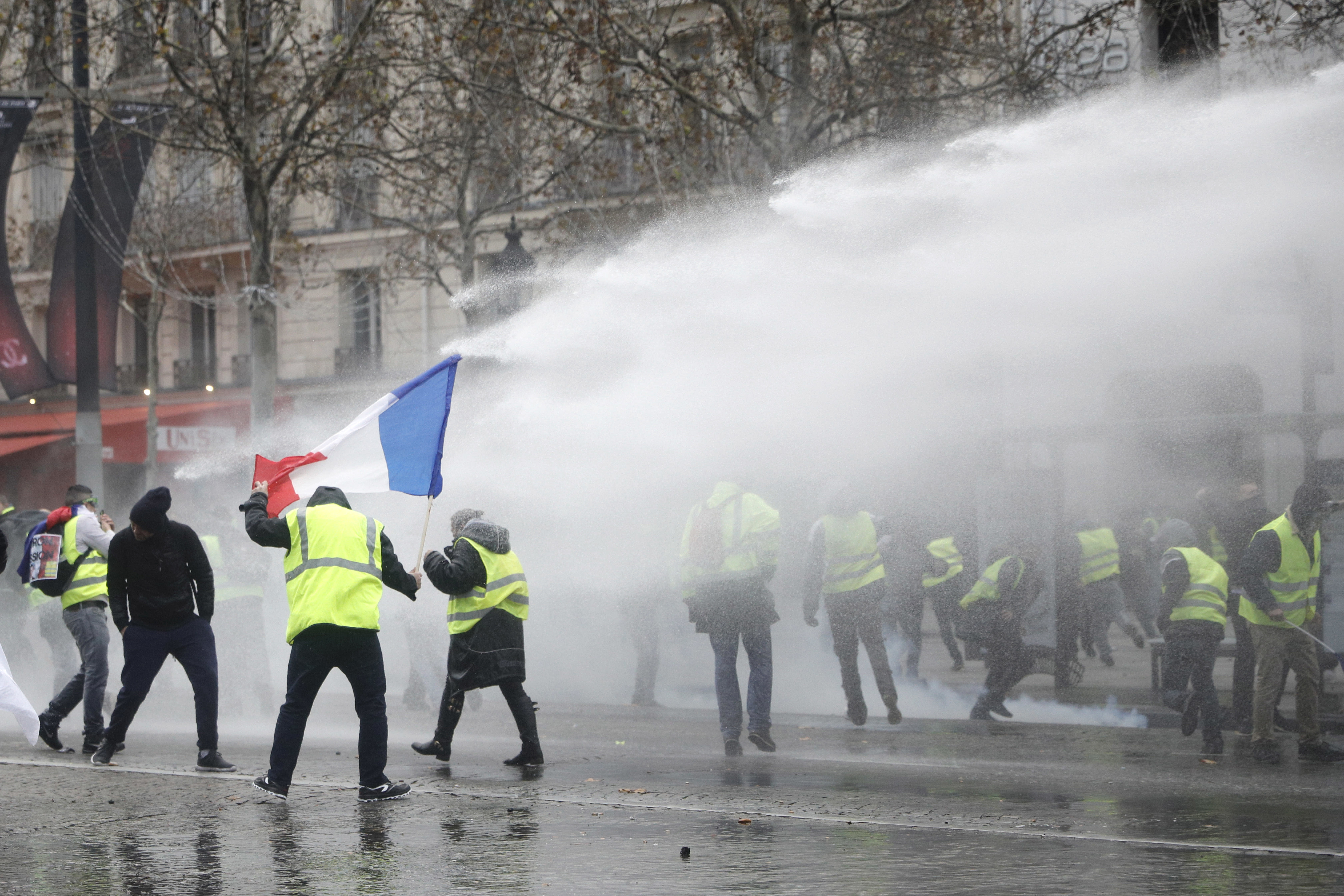 <p> Police operates a water canon during clashes with demonstrators, called the yellow jackets, on the famed Champs-Elysees avenue in Paris, as they protests against the rising of the fuel taxes, France, Saturday, Nov. 24, 2018. France is deploying thousands of police to try to contain nationwide protests and road blockades by drivers angry over rising fuel taxes and Emmanuel Macron's presidency. (AP Photo/Kamil Zihnioglu) </p>