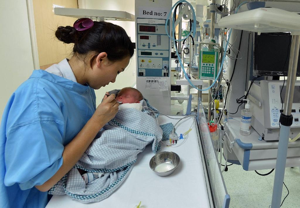 A baby born to a surrogate mother is fed by a nurse in a hospital in Kathmandu on May 26, 2015 (AFP Photo/Ishara S.Kodikara)