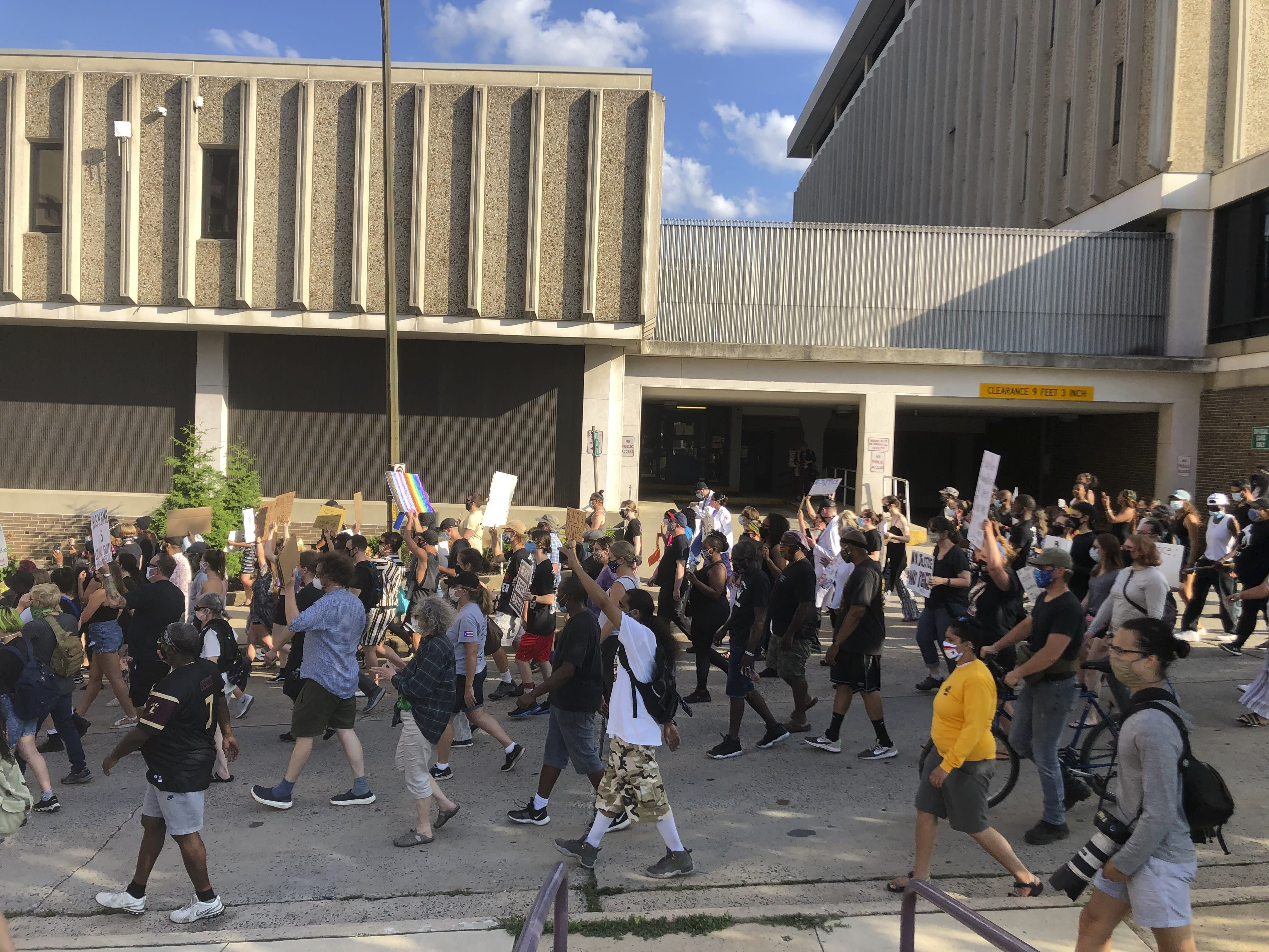 Protesters march past the police department in Allentown, Pennsylvania, on Monday, July 13, 2020, to demand accountability from police after video emerged of an officer placing his knee on a man's head and neck area outside a hospital. Police have launched an internal probe. (AP Photo/Michael Rubinkam)