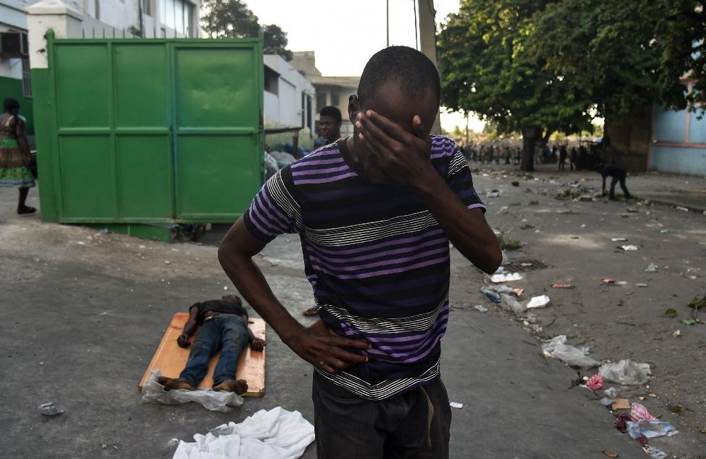 A man cries next to the body of a dead youth shot during clashes between Haitian police and demonstrators near the National Palace in Port-au-Prince, on February 9, 2019 (AFP Photo/HECTOR RETAMAL)