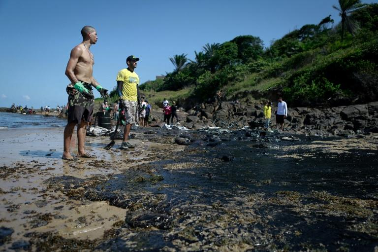 The oil has been seen along Brazil's northeastern Atlantic coast, including Pernambuco state, where volunteers are pictured cleaning up on October 21, 2019