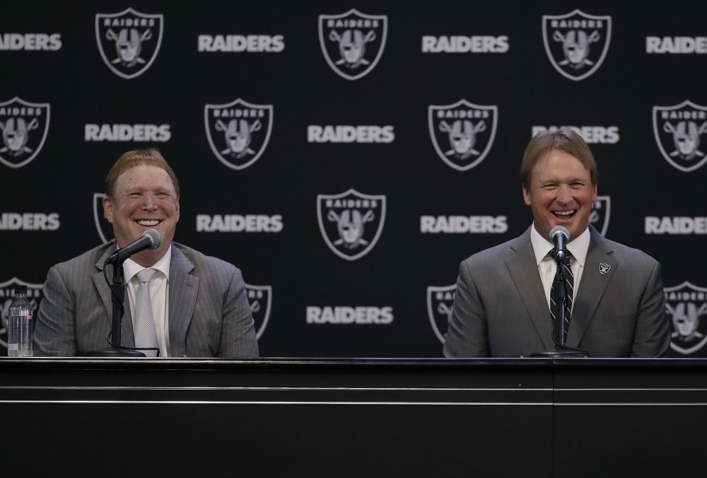 Oakland Raiders new head coach Jon Gruden, right, smiles as he sits next to owner Mark Davis. (AP)