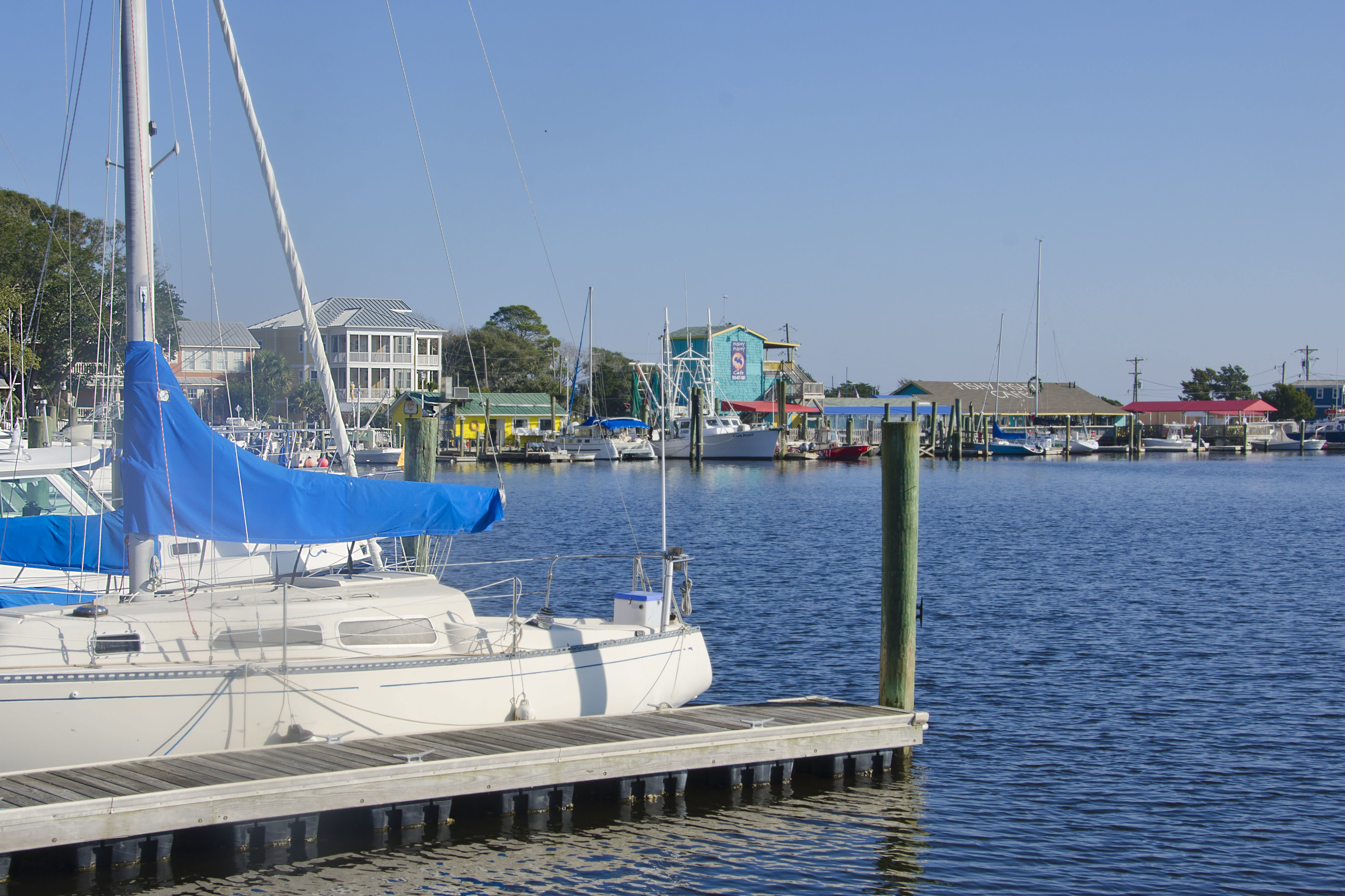 """<p>There's a reason this tiny harbor town at the outlet of the Cape Fear River was voted <a href=""""https://www.coastalliving.com/travel/top-10/2015-americas-happiest-seaside-towns?slide=160602#160602"""" rel=""""nofollow noopener"""" target=""""_blank"""" data-ylk=""""slk:America's Happiest Seaside Town in 2015"""" class=""""link rapid-noclick-resp"""">America's Happiest Seaside Town in 2015</a>. Bright white cottages with red roofs, stately sea captains' homes, two lighthouses, and water in seemingly every direction (what with the confluence of the river and the Intracoastal Waterway) create vistas at every bend in the road. It's a vintage postcard sent from a halcyon past.</p>"""