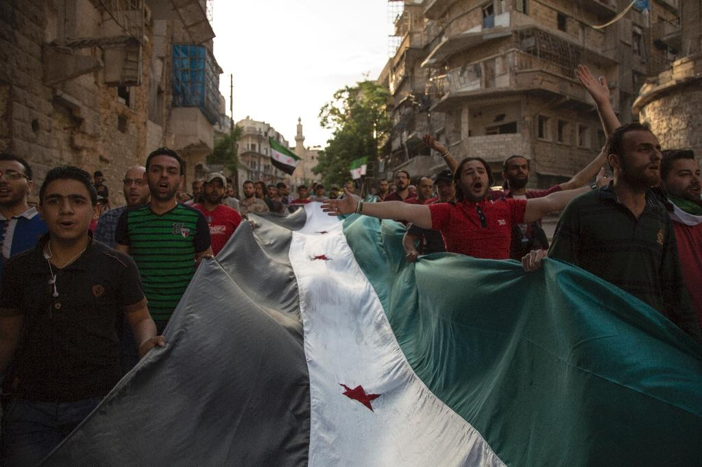 Syrians carry a giant pre-Baath Syrian flag as they shout slogans during an anti-regime protest in the rebel-held Bustan al-Qasr district in eastern Aleppo on May 5, 2016