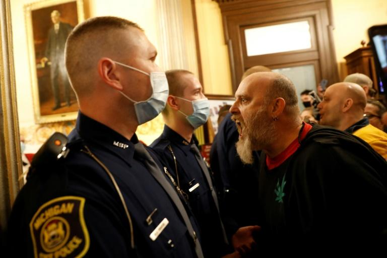 Protesters demanding an end to coronavirus lockdown orders tried to enter the House Chamber in the Michigan state capitol on April 30, 2020, but were blocked by state police (AFP Photo/JEFF KOWALSKY)