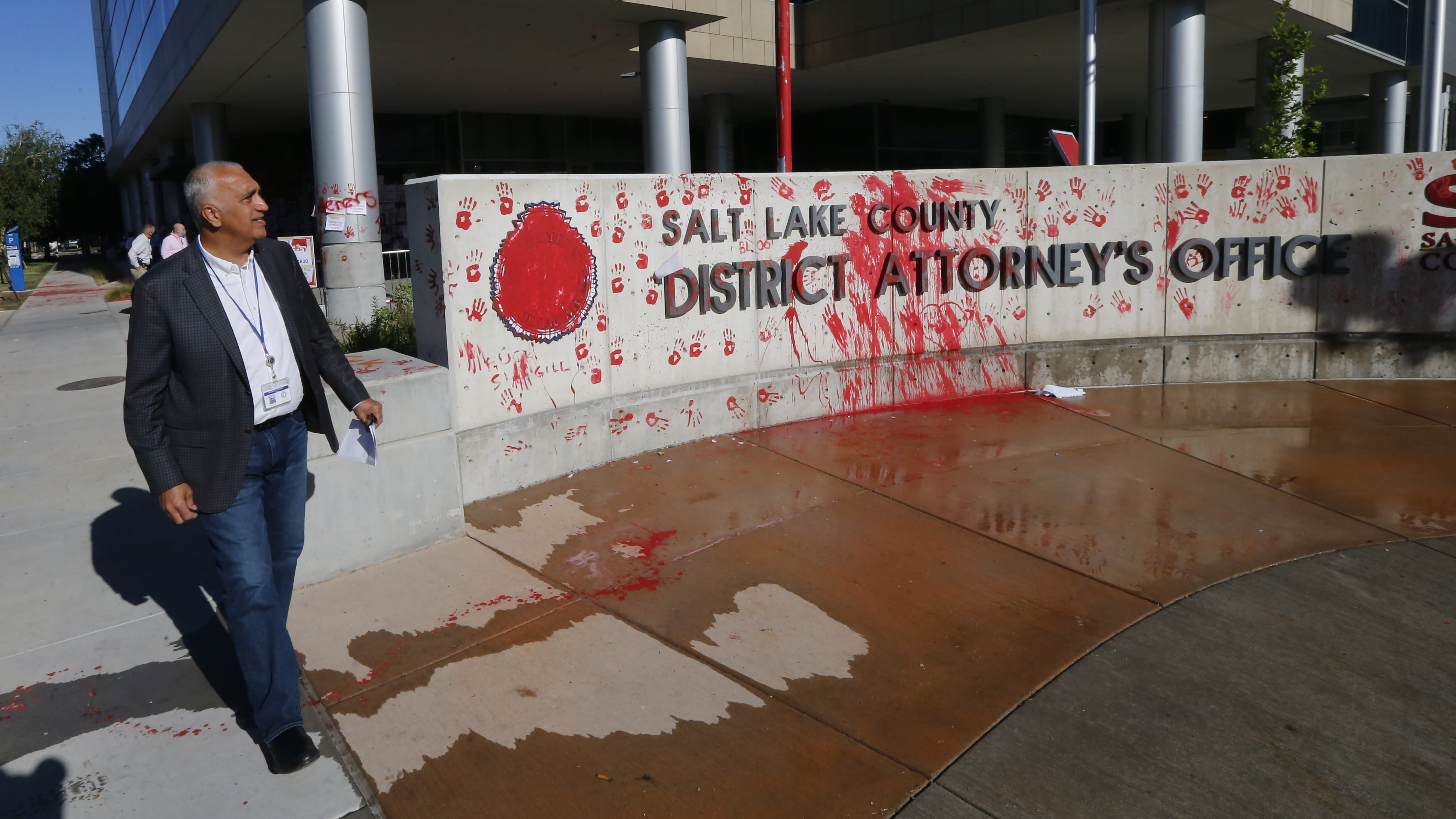 FILE - In this July 10, 2020, file photo, District Attorney Sim Gill inspects the damage to the district attorney's office in Salt Lake City. Some Black Lives Matter protesters in Utah could face up to life in prison if they're convicted of splashing red paint and smashing windows during a protest, a potential punishment that stands out among demonstrators arrested around the country and one that critics say doesn't fit the alleged crime. (AP Photo/Rick Bowmer, File)