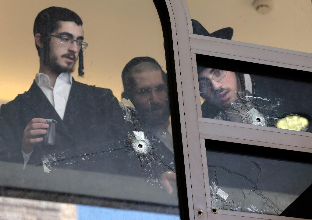 Ultra Orthodox Jews look on November 19, 2014 at bullet holes in the main window of a synagogue in Jerusalem where two Palestinians killed four rabbis and a policeman (AFP Photo/Thomas Coex)