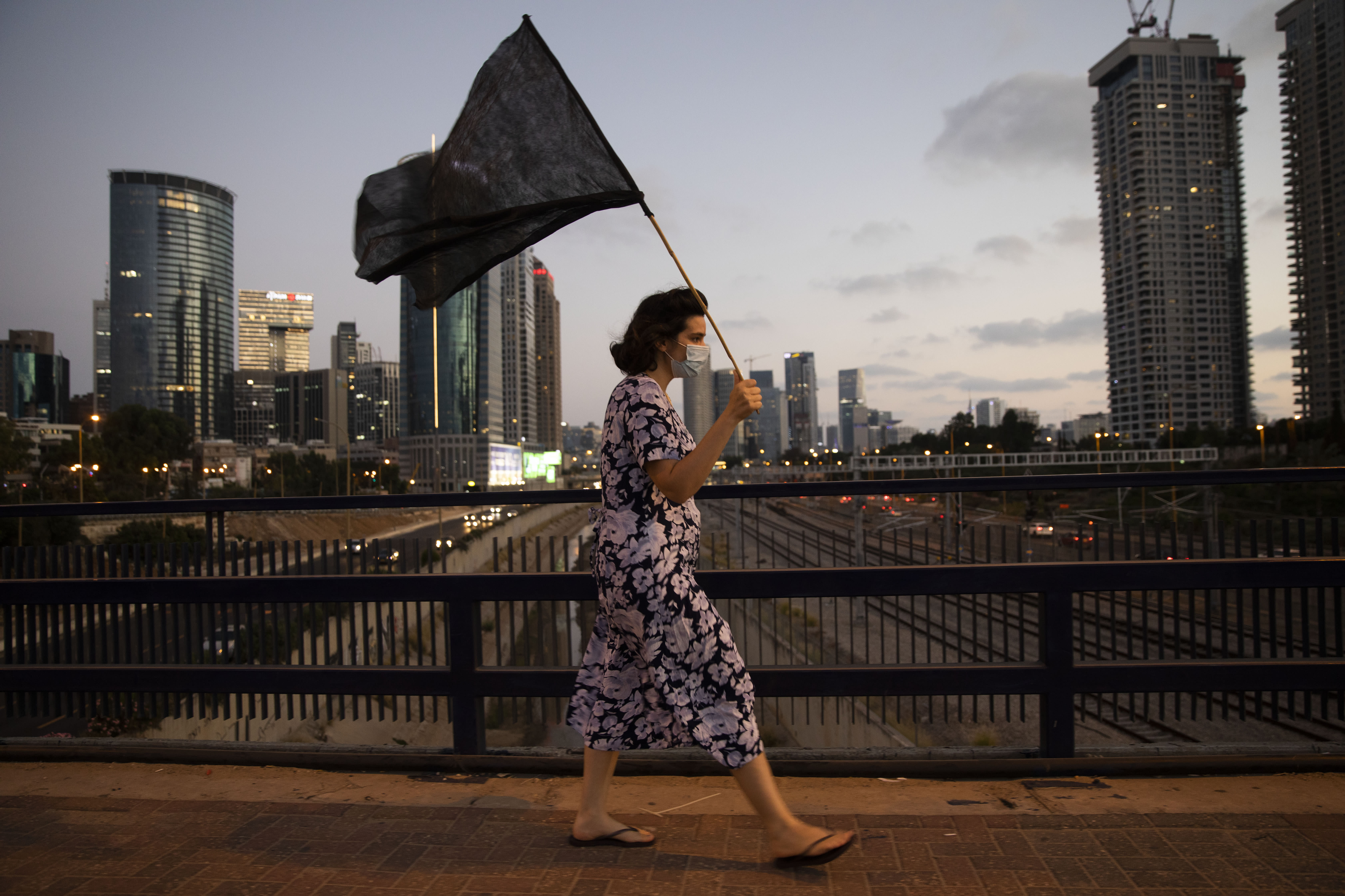 A woman wears a protective face mask, to protect against coronavirus, walks with a black flag during a protest against Israeli Prime Minister Benjamin Netanyahu, in Tel Aviv, Israel, Saturday, July 18, 2020. (AP Photo/Oded Balilty)