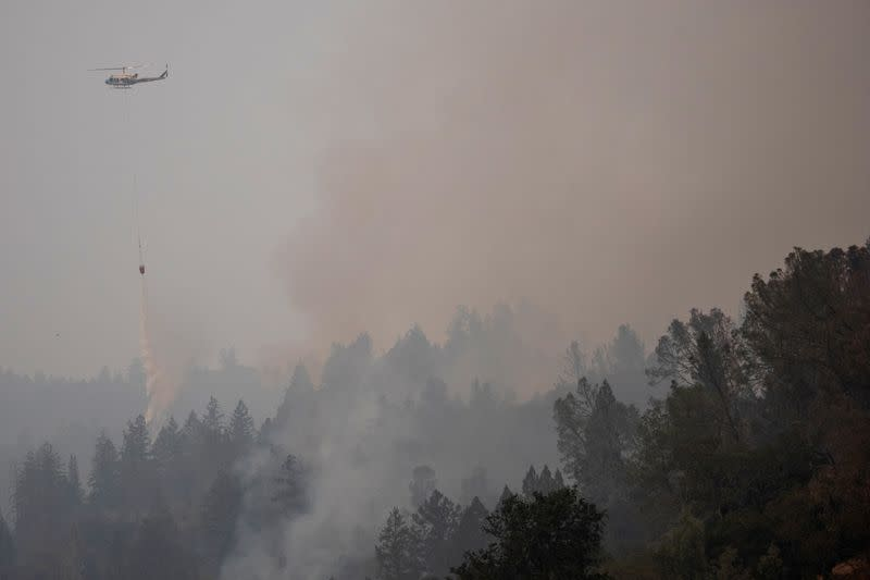 A helicopter drops water on the Glass Fire in Calistoga, California