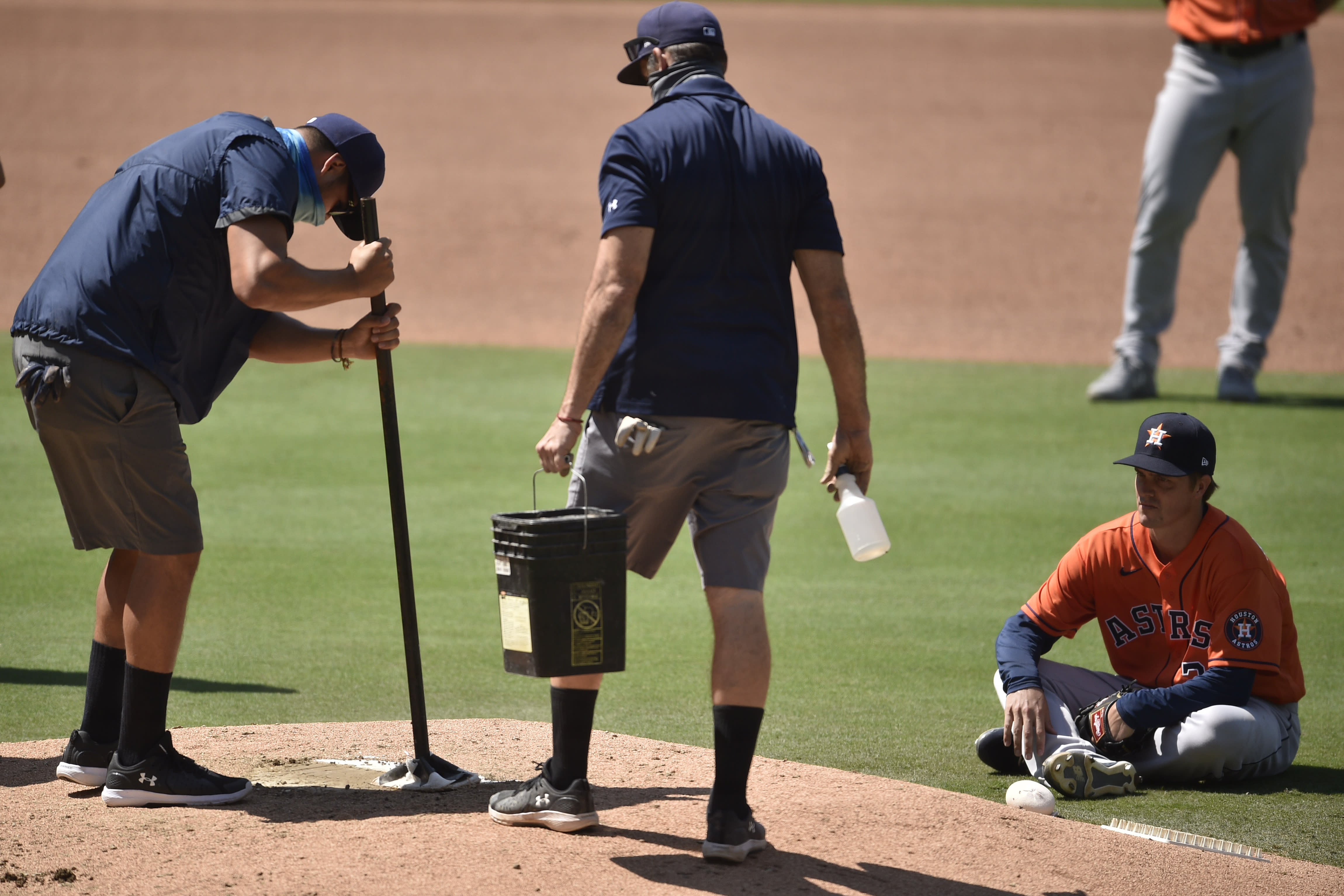 Houston Astros starting pitcher Zack Greinke, right, sits on the field as the San Diego Padres grounds crew work on the pitching mound during an in-game delay during the fourth inning of a baseball game in San Diego, Sunday, Aug. 23, 2020. (AP Photo/Kelvin Kuo)