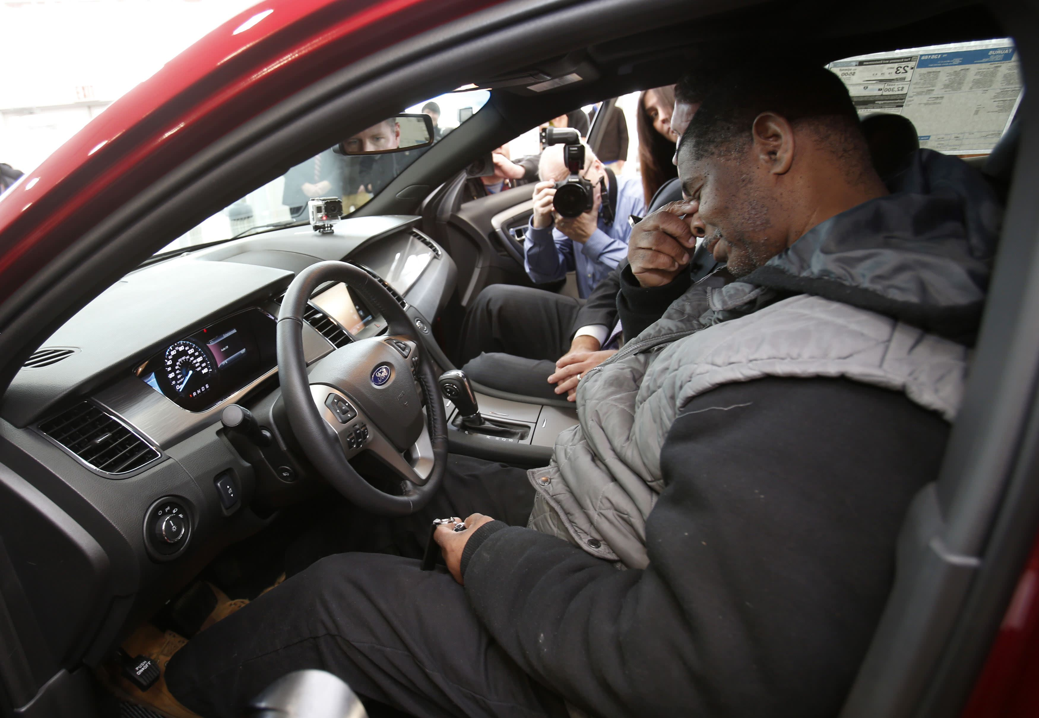 Detroit resident James Robertson sits in the drivers seat of the 2015 red Ford Taurus sedan he was surprised with as a free gift at the Suburban Ford dealership in Sterling Heights, Michigan, February 6, 2015. The 56-year-old factory worker, known for walking 21 miles to get to and from work for 9 years, is also the recipient of about $300,000 in donations raised by a college student after his story was widely publicized in local media. REUTERS/Rebecca Cook (UNITED STATES - Tags: TRANSPORT SOCIETY)