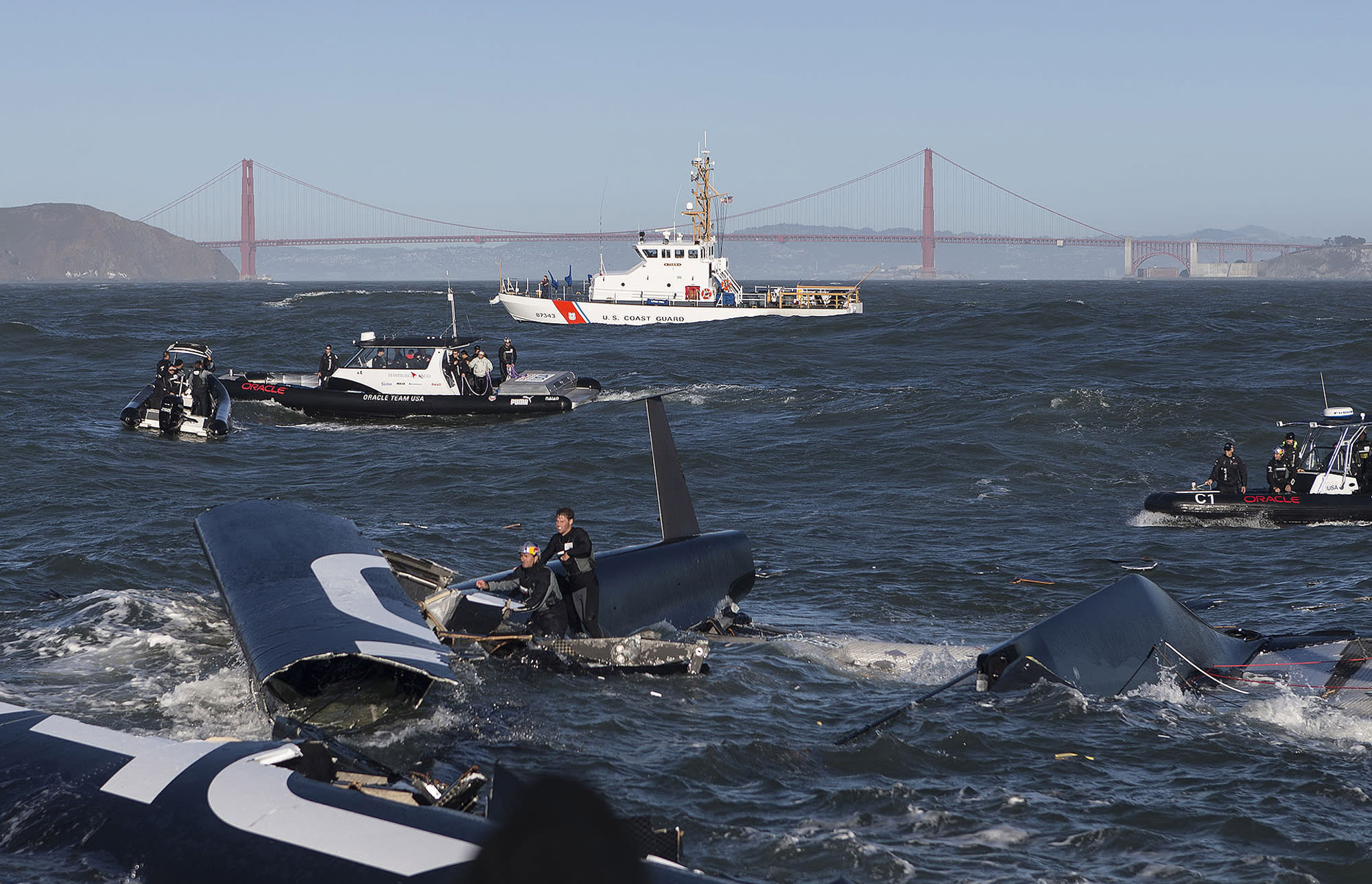 In this photo taken Tuesday Oct. 16, 2012 and provided by Oracle Team USA, crew members of the capsized Oracle Team USA AC72 boat are rescued after being swept past the Golden Gate Bridge in San Francisco. The America's Cup champion syndicate is assessing the damage to its 72-foot (22-meter) catamaran, after it capsized and was swept by a strong current more than four miles (six kilometers) past the Golden Gate Bridge before rescue boats could control it.(AP Photo/Oracle Team USA, Guilain Grenier) MANDATORY CREDIT