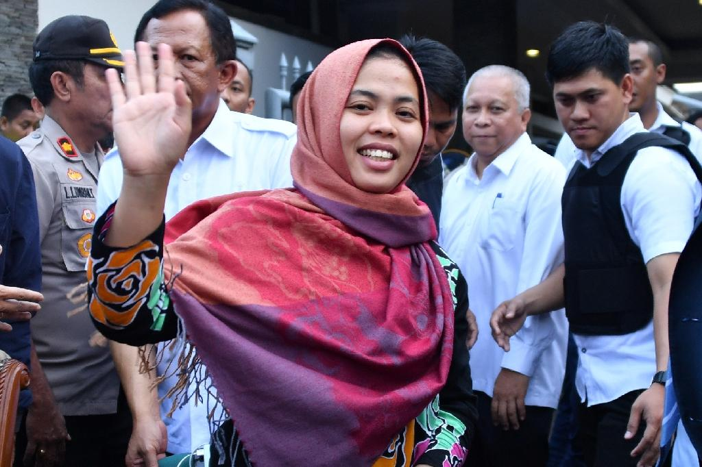 Indonesian Siti Aisyah waves to the press after her return to Jakarta having been freed by a Malaysian court (AFP Photo/ADEK BERRY)