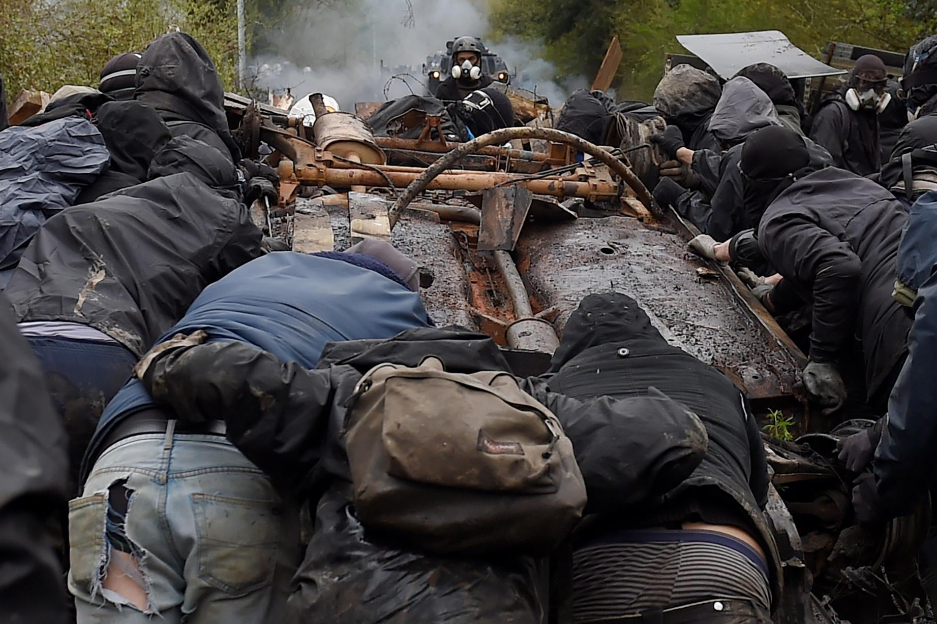 <p>Protesters push the wreckage of a car to build barricade as clashes erupt with riot forces on April 10, 2018 during a police operation to raze the decade-old camp known as ZAD (Zone a Defendre – Zone to defend) at Notre-Dame-des-Landes, near the western city of Nantes, and evict the last of the protesters who had refused to leave despite the government agreeing to ditch a proposed airport. (Photo: Guillaume Souvant/AFP/Getty Images) </p>
