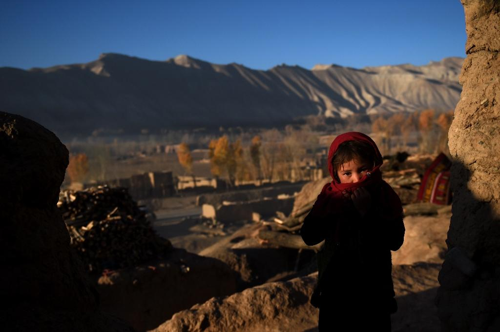 An Afghan Hazara girl stands in front of the cave where she lives with her family in the old city of Bamiyan (AFP Photo/Wakil Kohsar)