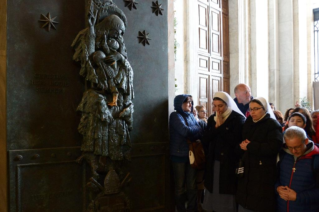 """Worshipers pass by a """"Holy Door"""" opened by Pope Francis at St John Lateran basilica on December 13, 2015 at the Vatican (AFP Photo/Vincenzo Pinto)"""
