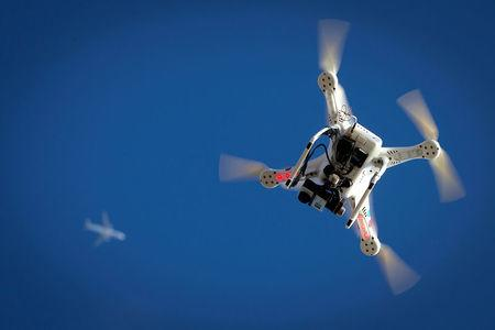 FILE PHOTO: An airplane flies over a drone during the Polar Bear Plunge on Coney Island in the Brooklyn borough of New York, U.S., January 1, 2015. REUTERS/Carlo Allegri/File Photo