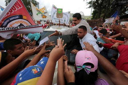 """Venezuela's President Nicolas Maduro greets supporters as he arrives for his weekly broadcast """"En contacto con Maduro"""" (In contact with Maduro) in La Victoria"""