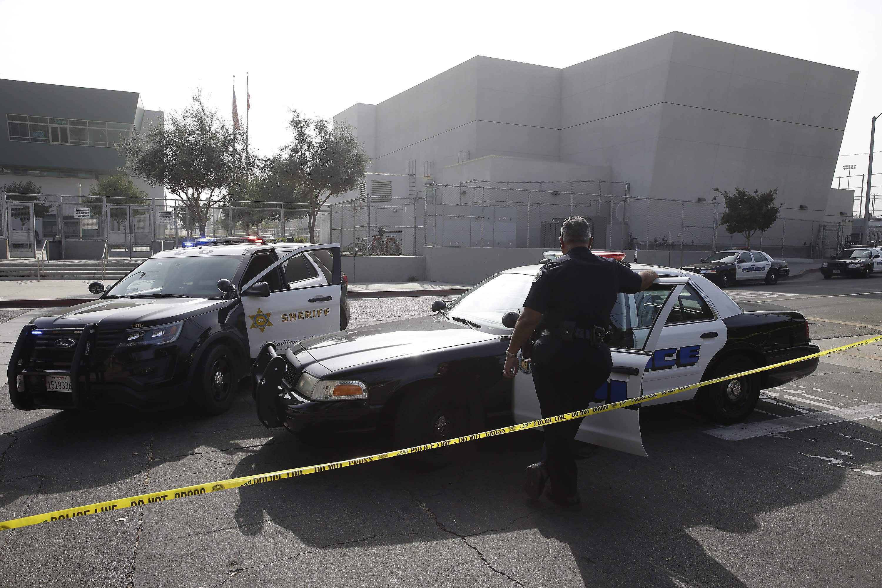 FILE - Los Angeles Sheriffs officers and Los Angeles Unified School District police officers guard the campus of Esteban Torres High School in unincorporated East Los Angeles, after a sheriff's deputy fatally shot a man wielding a sword, after he had climbed over the fence to get onto the school grounds Wednesday, Nov. 13, 2019. On Tuesday, June 30, 2020, the Los Angeles Unified School District voted an immediate 35% cut to the budget of its school police. (AP Photo/Damian Dovarganes, File)