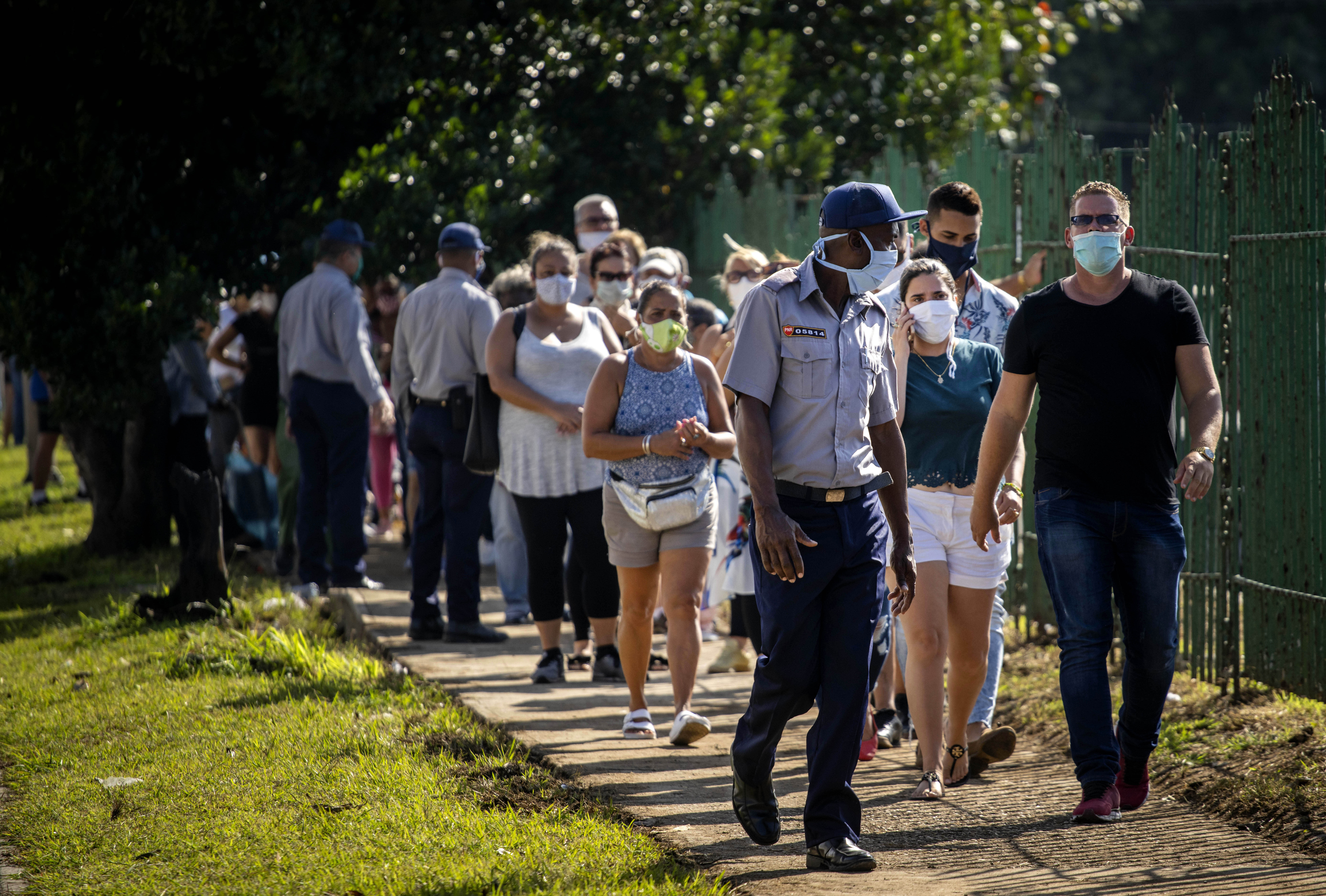 People wearing protective face masks as a precaution amid the spread of the new coronavirus line up to enter a grocery store that accepts U.S. dollars in Havana, Cuba, Monday, July 20, 2020. Cuba has expanded the types of stores that accept dollars for payment to include food stores, as part of the government's effort to capture much needed hard currency to shore up the island's ailing economy. (AP Photo/Ramon Espinosa)