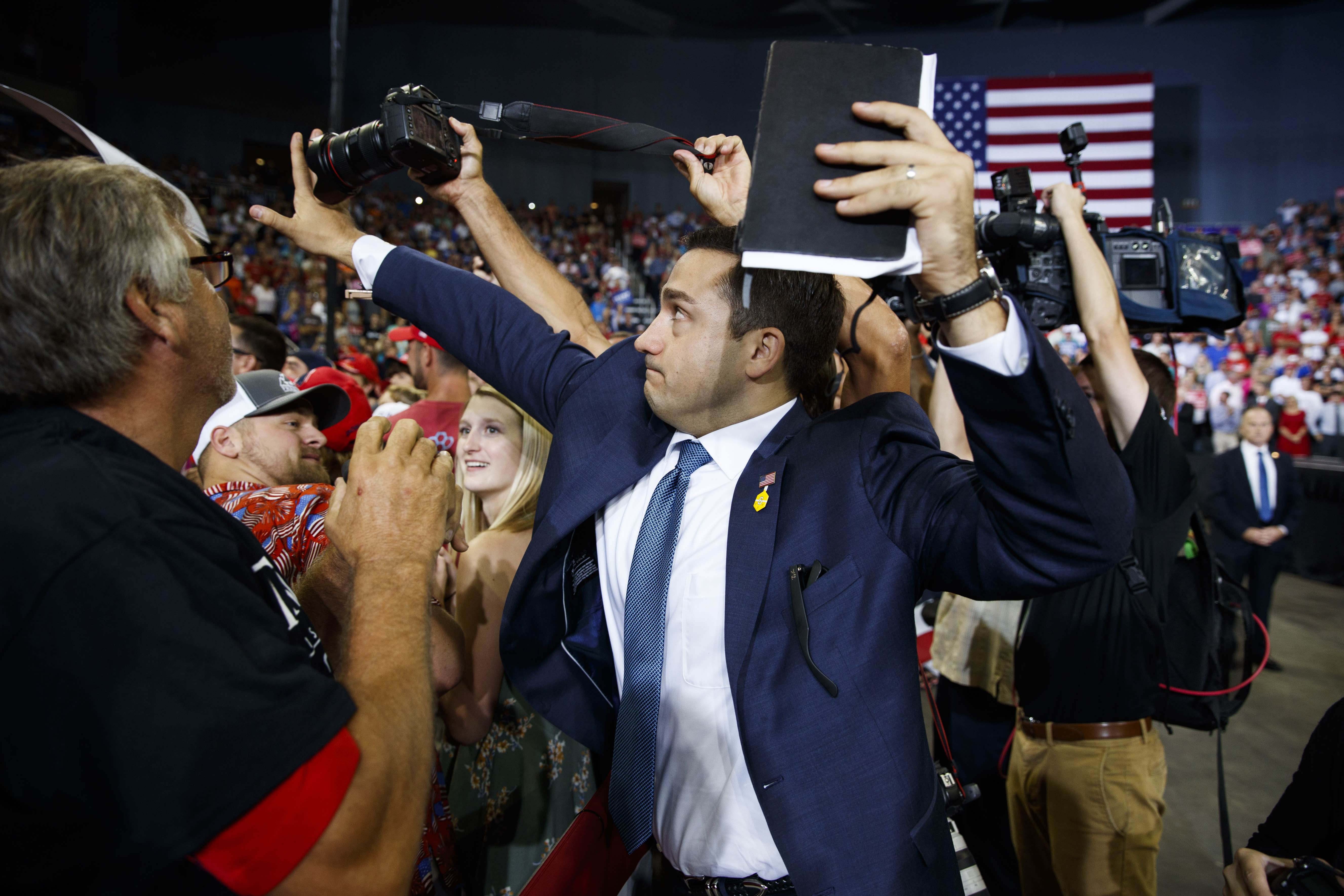 ADDS THAT MAN BLOCKING CAMERA IS A VOLUNTEER - A volunteer member of the advance team for President Donald Trump blocks a camera as a photojournalist attempts to take a photo of a protester during a campaign rally at the Ford Center, Thursday, Aug. 30, 2018, in Evansville, Ind. (AP Photo/Evan Vucci)