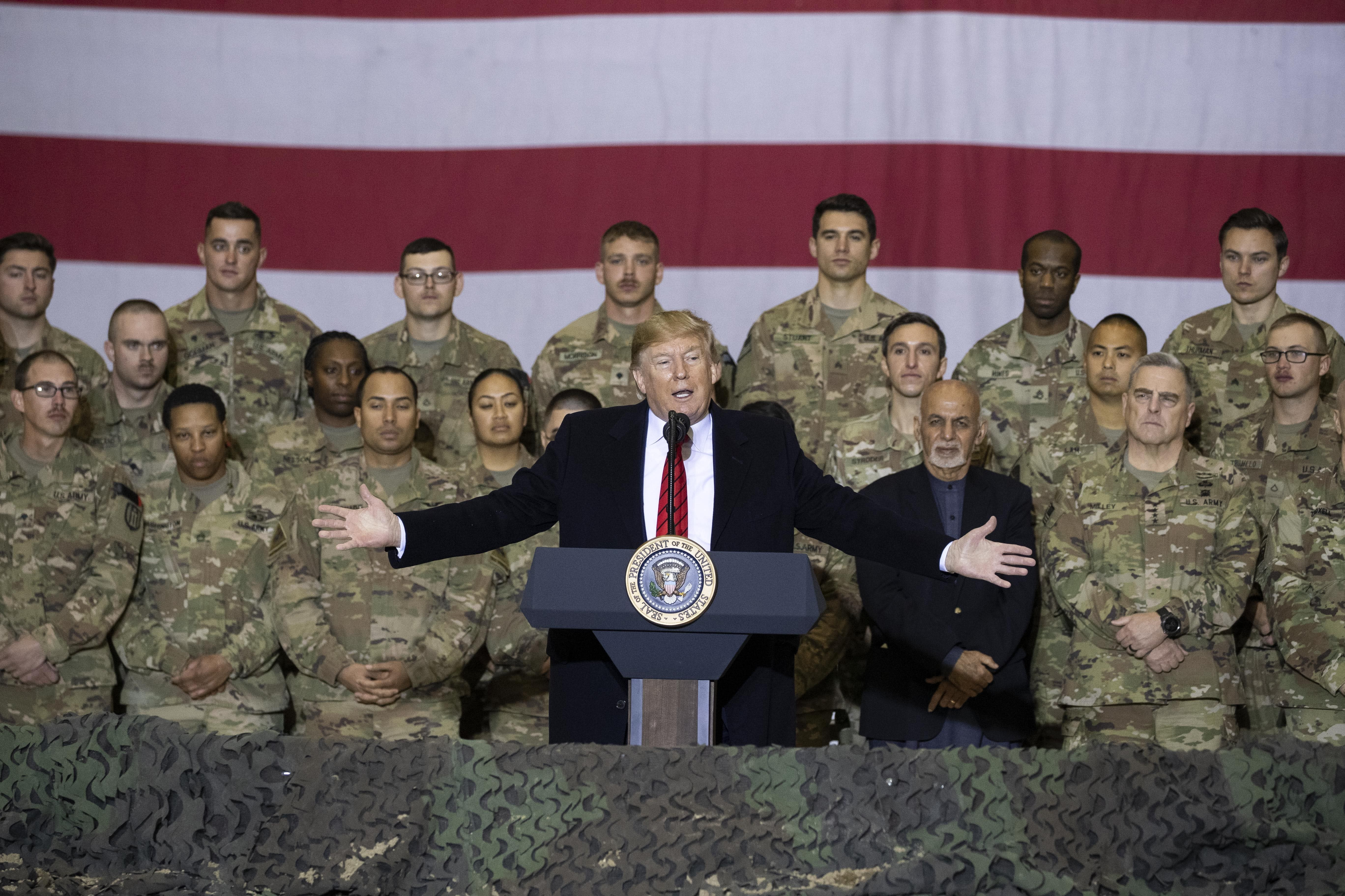 President Donald Trump, center, with Afghan President Ashraf Ghani and Joint Chiefs Chairman Gen. Mark Milley, behind him at right, addresses members of the military during a surprise Thanksgiving Day visit at Bagram Air Field, Afghanistan on Nov. 28, 2019. (Alex Brandon/AP)