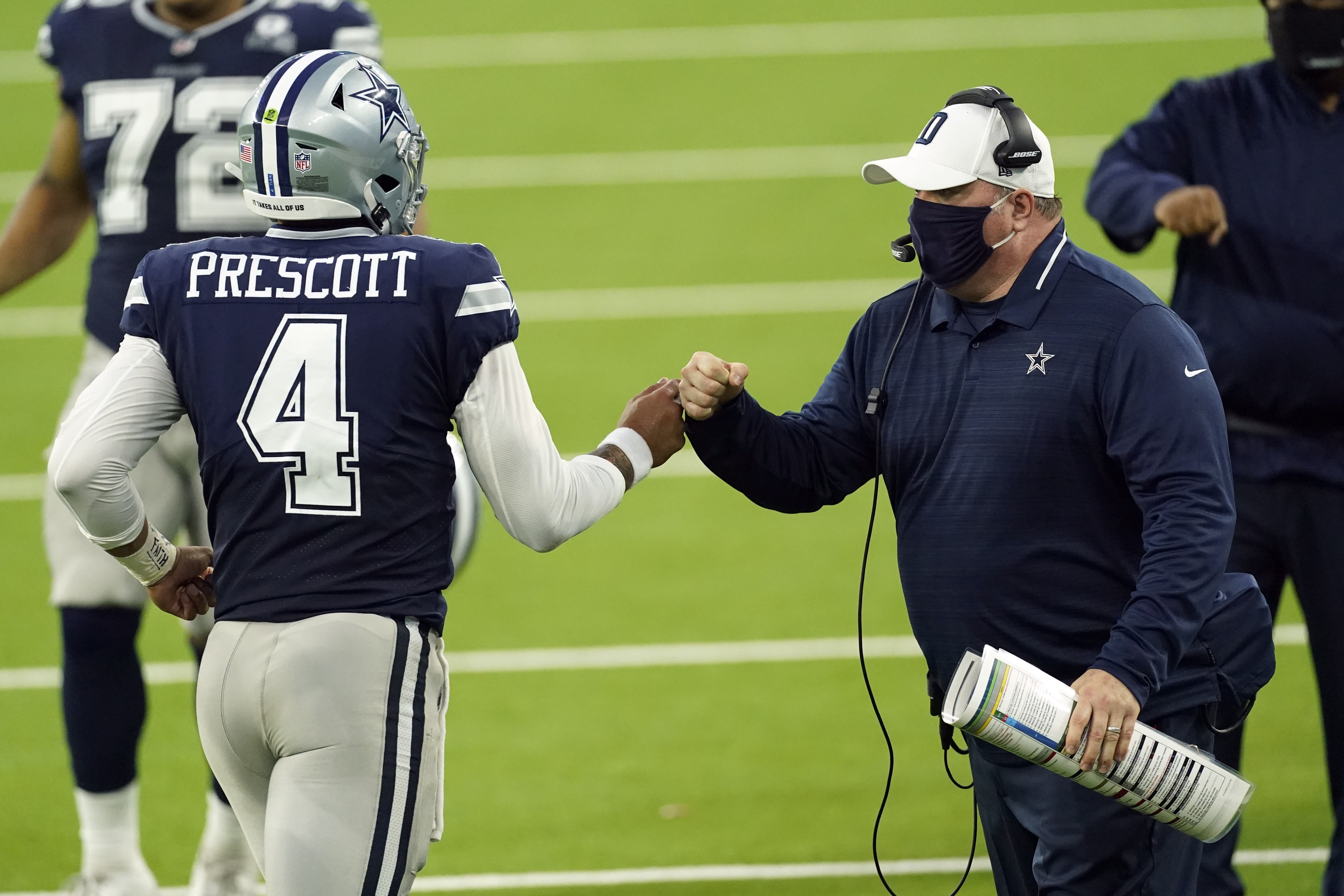 Dallas Cowboys head coach Mike McCarthy bumps fists with quarterback Dak Prescott (4) during the first half of an NFL football game against the Los Angeles Rams Sunday, Sept. 13, 2020, in Inglewood, Calif. (AP Photo/Ashley Landis )