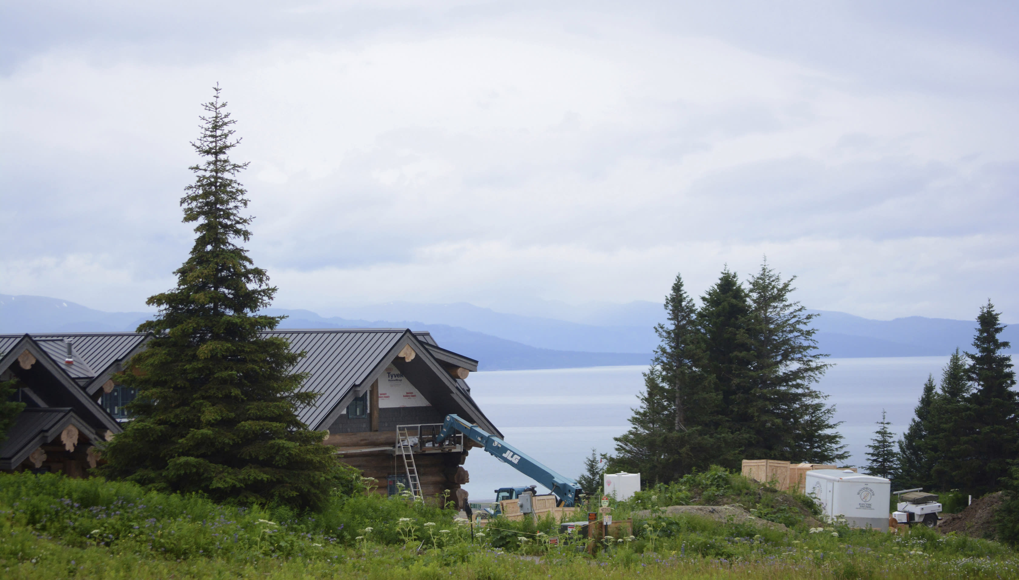 This July 9, 2019 photo shows part of country musician Zac Brown's log home, visible from Dorothy Drive overlooking Kachemak Bay in Homer, Alaska. Brown has lost a bid to limit public access to his property. Brown had asked the Kenai Peninsula Borough Planning Commission to remove easements allowing the access along his property in hills above Homer, a small city on Kachemak Bay on Alaska's Kenai Peninsula, KSRM-AM reported Tuesday, Aug. 13, 2019. The commission voted 5-4 against Brown's request Monday following more than two hours of public testimony. (Michael Armstrong/Homer News via AP)