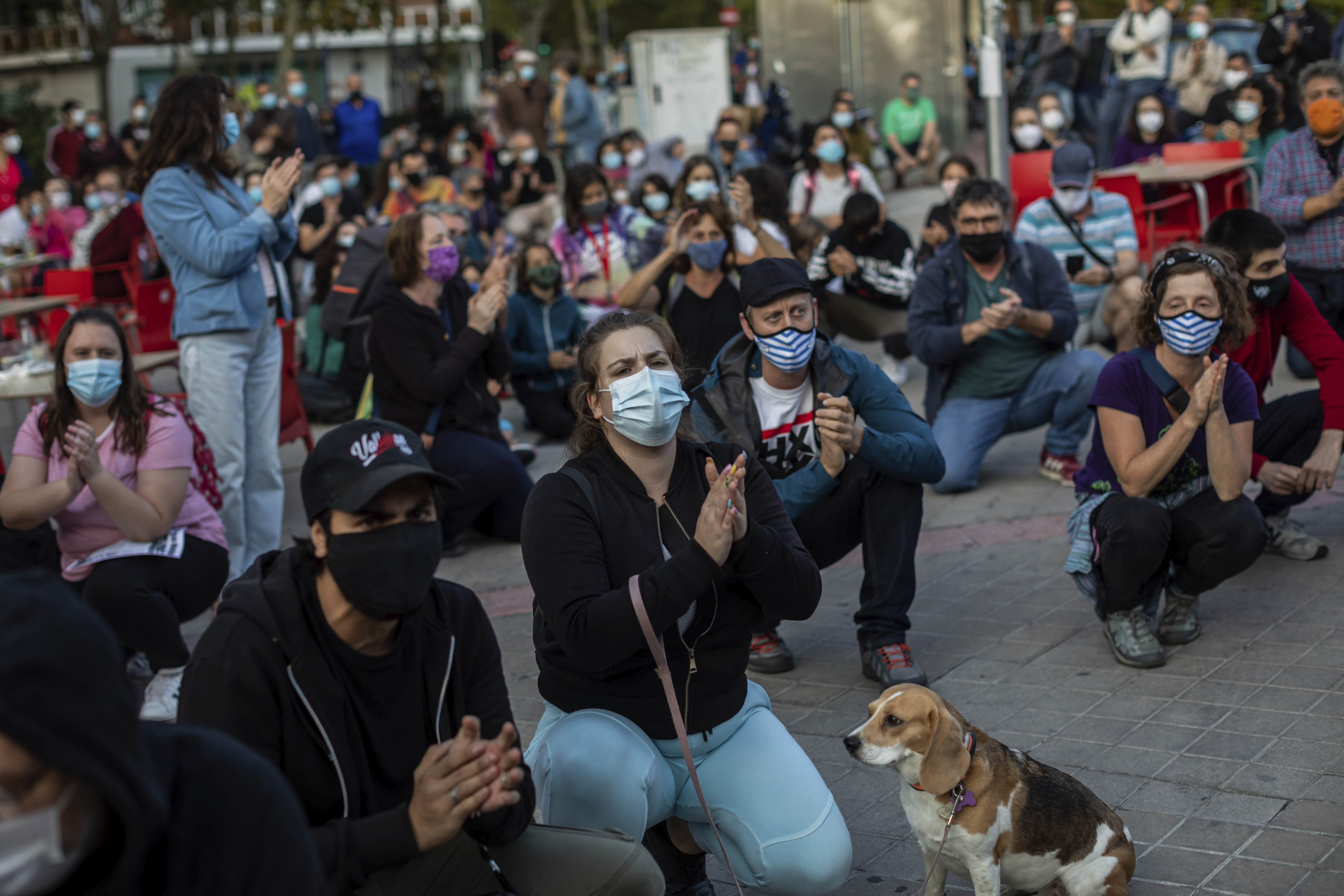 Residents of restricted mobility areas in Madrid due to the coronavirus outbreak gather during a protest to demand more resources for public health system and against social inequality in the southern neighbourhood of Vallecas, Madrid, Spain, Thursday, Sept. 24, 2020. The regional government is set to announce Friday new restrictions in Madrid, where gatherings are limited to a maximum of 6 people and more than 850,000 residents have been partially locked down this week. (AP Photo/Bernat Armangue)