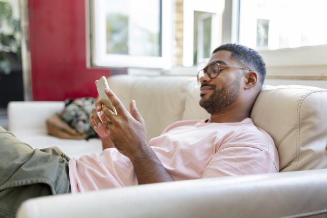 Relaxed man sitting on sofa using cell phone
