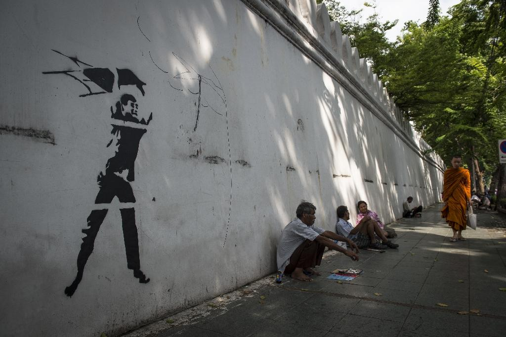 Graffiti depicting a violent ultra-royalist with a chair from the iconic photograph of the October 6, 1976 student massacre by Associated Press photographer Neil Ulevich, seen on the outside wall of Thammasat University in Bangkok