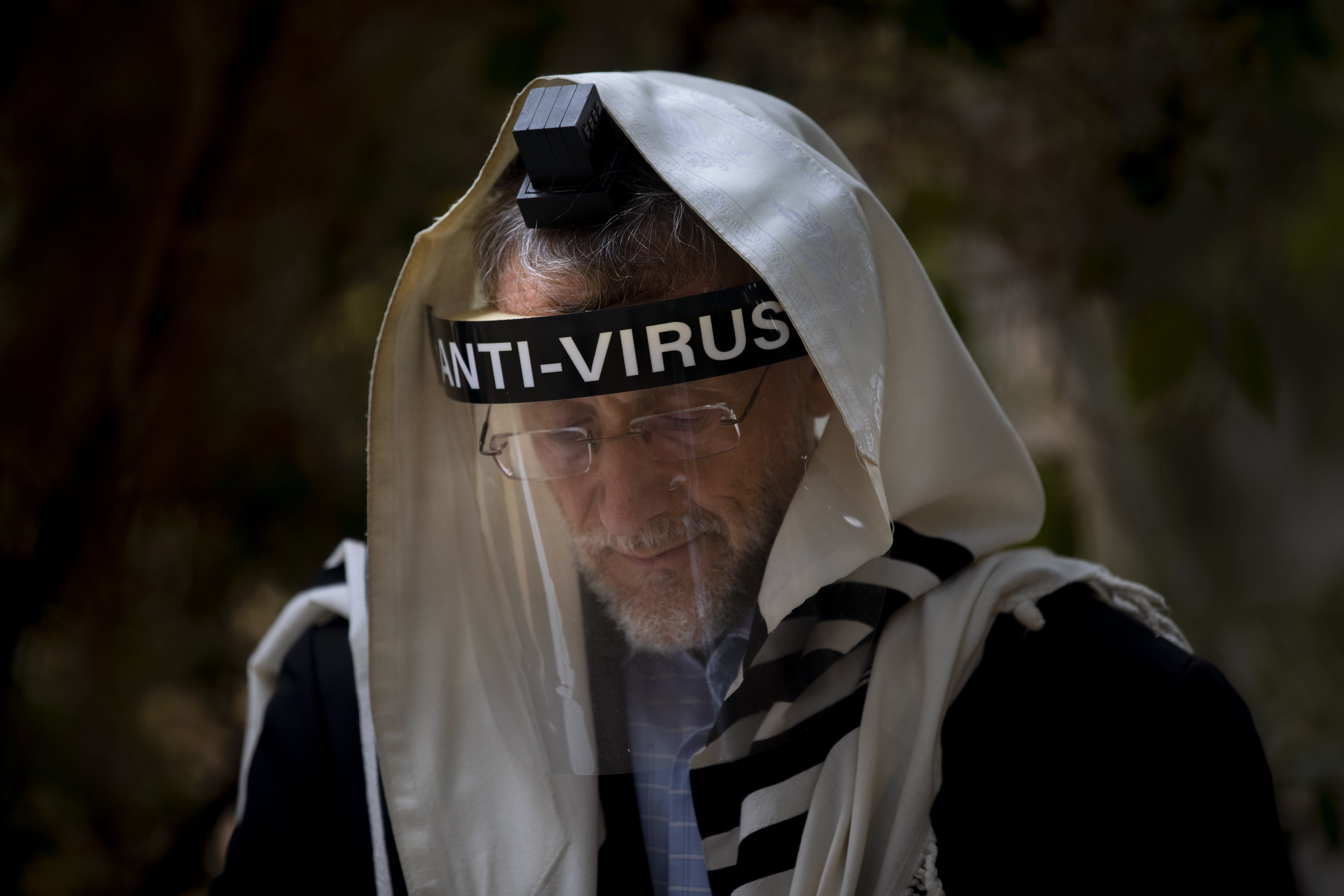 An Ultra-Orthodox Jewish man wears a face mask during a morning prayer next to his house as synagogues are limited to twenty people during a nationwide three-week lockdown to curb the spread of the coronavirus, in Bnei Brak, Israel, Thursday, Sept 24, 2020. Israel moved to further tighten its second countrywide lockdown as coronavirus cases continued to soar. The Cabinet voted to close all nonessential businesses, including open-air markets. Prayers and political demonstrations would be limited to open spaces and no more than 20 people, and participants would not be able to travel more than a kilometer (0.6 miles) from home for either. (AP Photo/Oded Balilty)