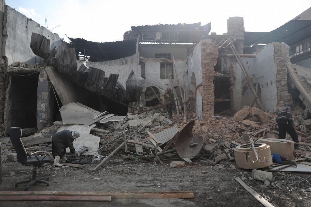 Syrian men inspect the rubble of a destroyed house in the rebel-held town of Douma, on the eastern outskirts of Damascus, on December 30, 2016