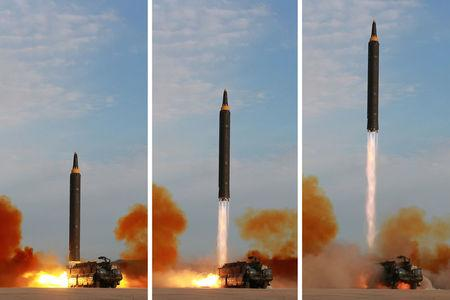North Korean leader Kim Jong Un guides the launch of a Hwasong-12 missile in this undated combination photo released by North Korea's KCNA