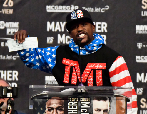 Floyd Mayweather holds up a check during the first news conference for his fight against Conor McGregor. (Getty)