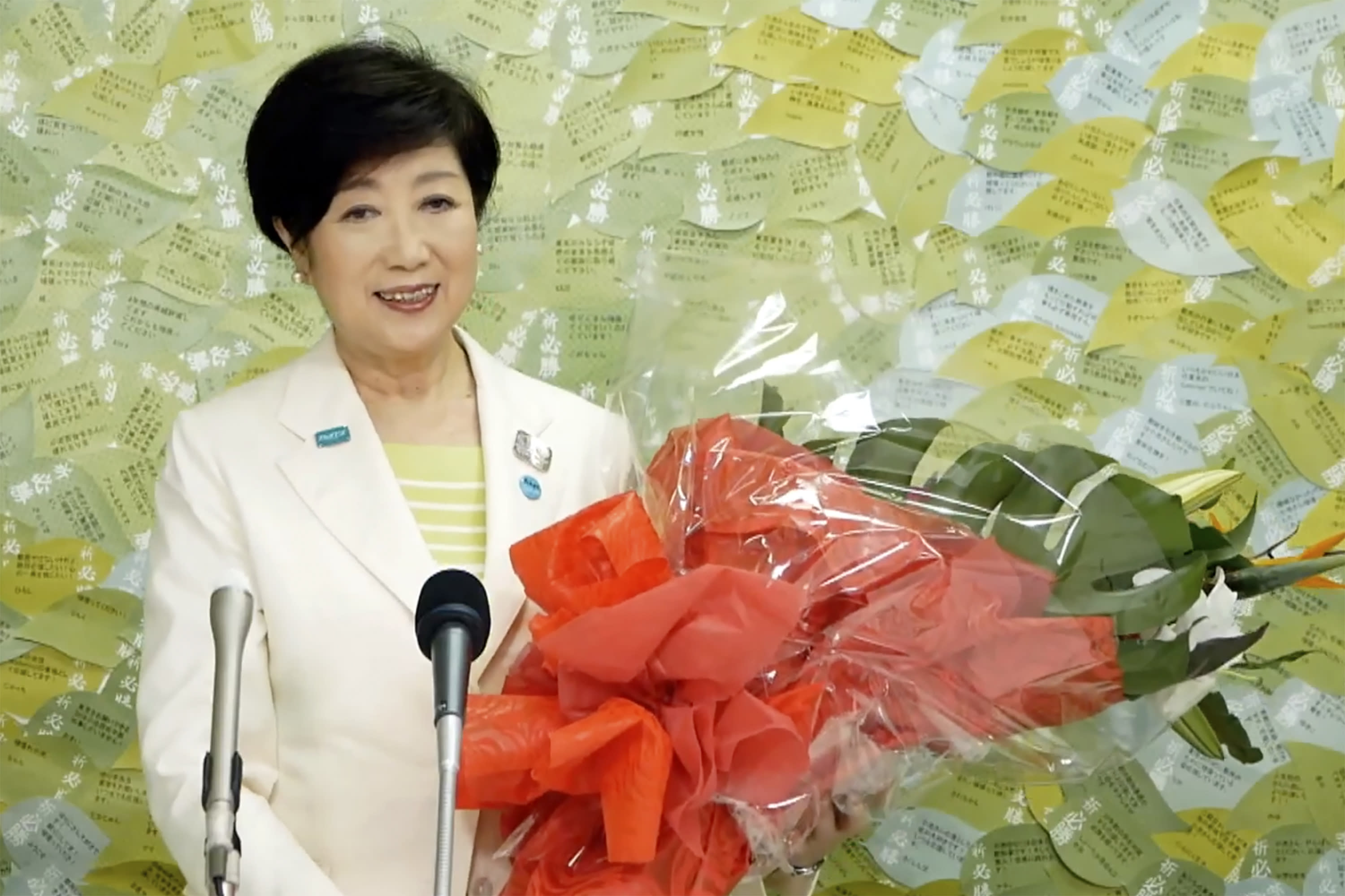 In this image made from YouTube provided by Koike Yuriko Official Channel, Tokyo Gov. Koike recieves a bunch of flower from supporter during her gubernatorial election victory press conference at her election office in Tokyo, Sunday, July 5, 2020. (Koike Yuriko Official Channel via AP)