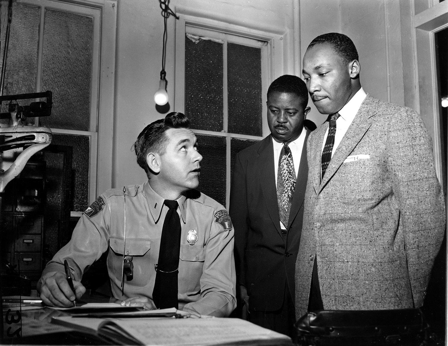 <p>The Rev. Martin Luther King Jr., right, accompanied by Rev. Ralph D. Abernathy, center, is booked by city police Lt. D.H. Lackey in Montgomery, Ala., on Feb. 23, 1956. The civil rights leaders are arrested on indictments turned by the Grand Jury in the bus boycott. (AP Photo/Gene Herrick) </p>