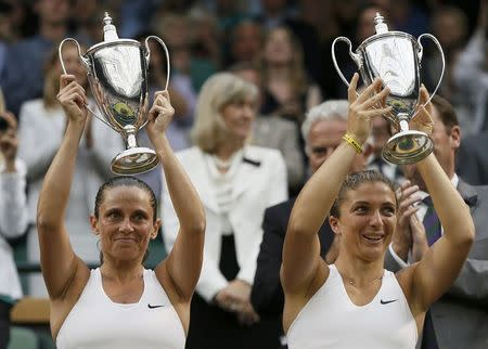 Sara Errani of Italy and Roberta Vinci of Italy celebrate with their winners trophies after defeating Timea Babos of Hungary and Kristina Mladenovic of France in their women's doubles tennis match at the Wimbledon Tennis Championships, in London