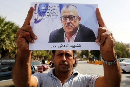 A relative of the Jordanian writer Nahed Hattar holds his picture during a sit-in in the town of Al-Fuheis near Amman, Jordan, September 25, 2016. REUTERS/Muhammad Hamed