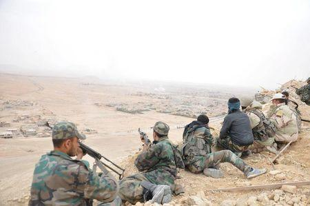 Forces loyal to Syria's President Bashar al-Assad take positions on a look-out point overlooking the historic city of Palmyra in Homs Governorate