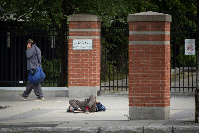 A pedestrian walks past a passed-out drug user on June 25, 2020 in Ottawa, Canada; an emergency government pandemic payment has been used by some addicts to buy drugs, and overdoses have surged (AFP Photo/Lars Hagberg)