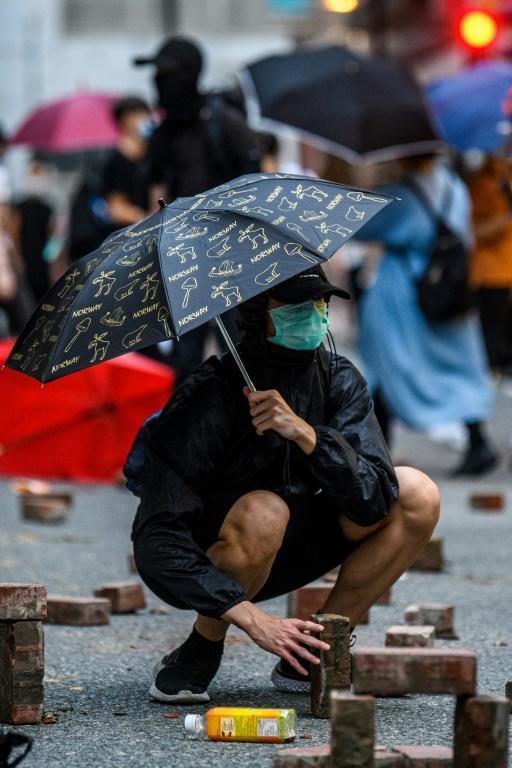 A protester places bricks that were dug up from a nearby sidewalk onto a road during a rally against a new national security law in Hong Kong on July 1, 2020 (AFP Photo/Anthony WALLACE)