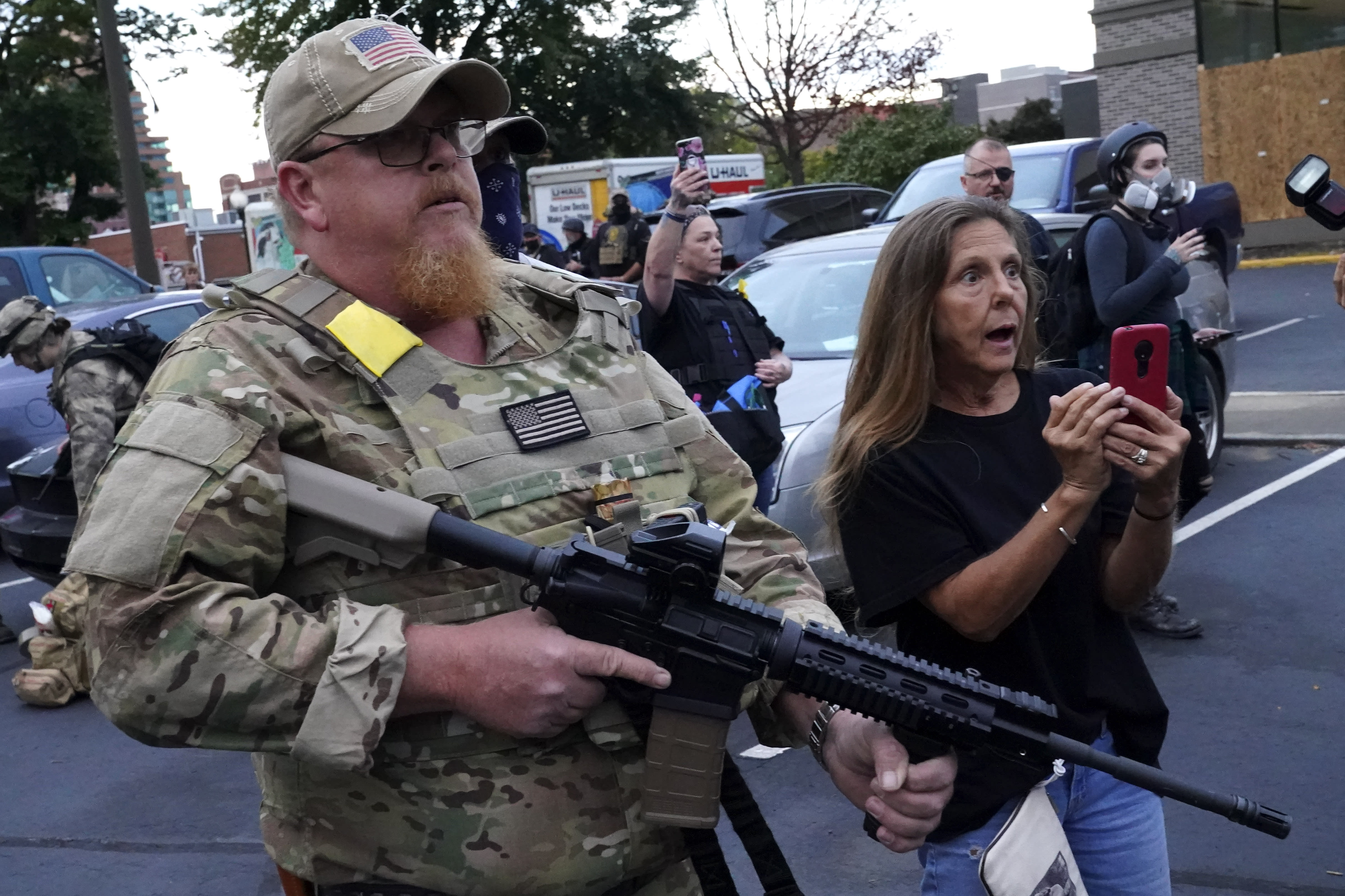 An armed counter-protester speaks with Black Lives Matter demonstrators, Thursday, Sept. 24, 2020, in Louisville, Ky. Authorities pleaded for calm while activists vowed to fight on Thursday in Kentucky's largest city, where a gunman wounded two police officers during anguished protests following the decision not to charge officers for killing Breonna Taylor. (AP Photo/John Minchillo)