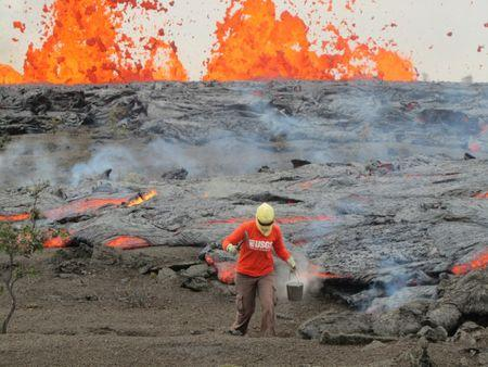 A geologist is collecting sample of molten lava from 2011 Kamoamoa eruption, at Kilauea Volcano, Hawaii, U.S., March 6, 2011. Picture taken on March 6, 2011. Courtesy USGS/Handout via REUTERS