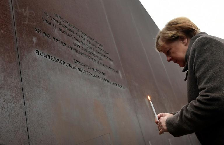 German Chancellor Angela Merkel places a candle at the Berlin Wall Memorial during the central commemoration ceremony for the 30th anniversary of the fall of the Berlin Wall in Berlin, Germany (AFP Photo/Tobias SCHWARZ)