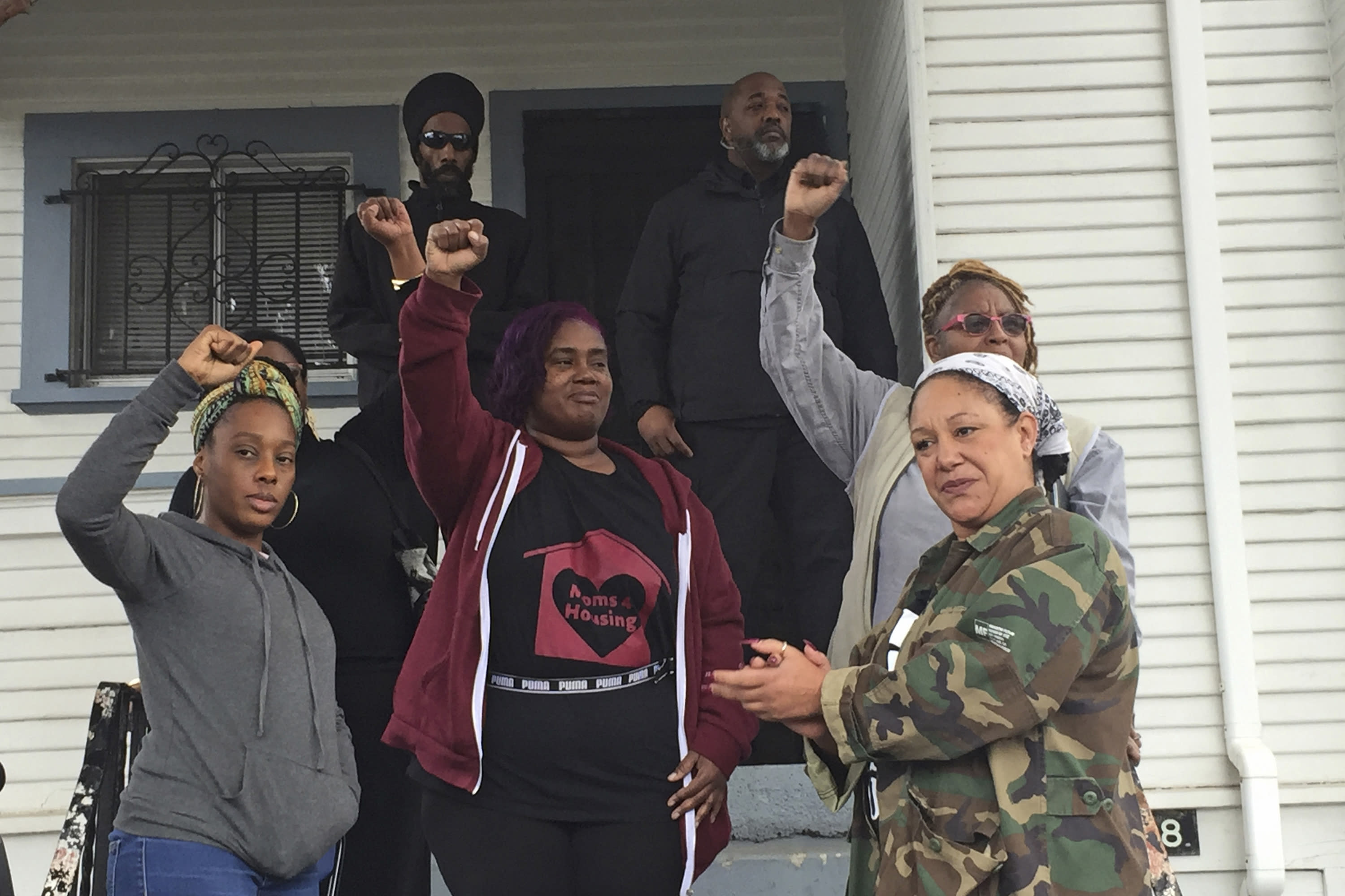 """In this Dec. 6, 2019 photo, Moms 4 Housing member Dominique Walker, 34, left, activist and 2018 Oakland mayoral candidate Cat Brooks, right, and other activists react as supporters chant """"power to the moms"""" outside a home in West Oakland, Calif. Walker and other homeless women took over the vacant house and moved in last November. They are awaiting a final ruling from a judge on whether they can stay, though Alameda County Superior Court Judge Patrick McKinney has tentatively ruled in favor of the property owner, Wedgewood Inc.(Marissa Kendal/Bay Area News Group via AP)"""