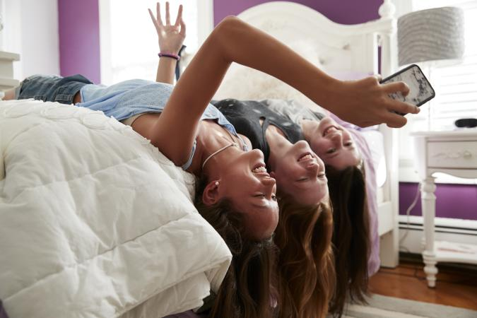 Three teenage girls lying on bed taking a selfie upside down