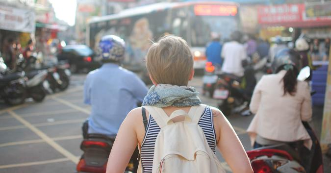 Stock image of a person photographed from behind wearing a backpack.