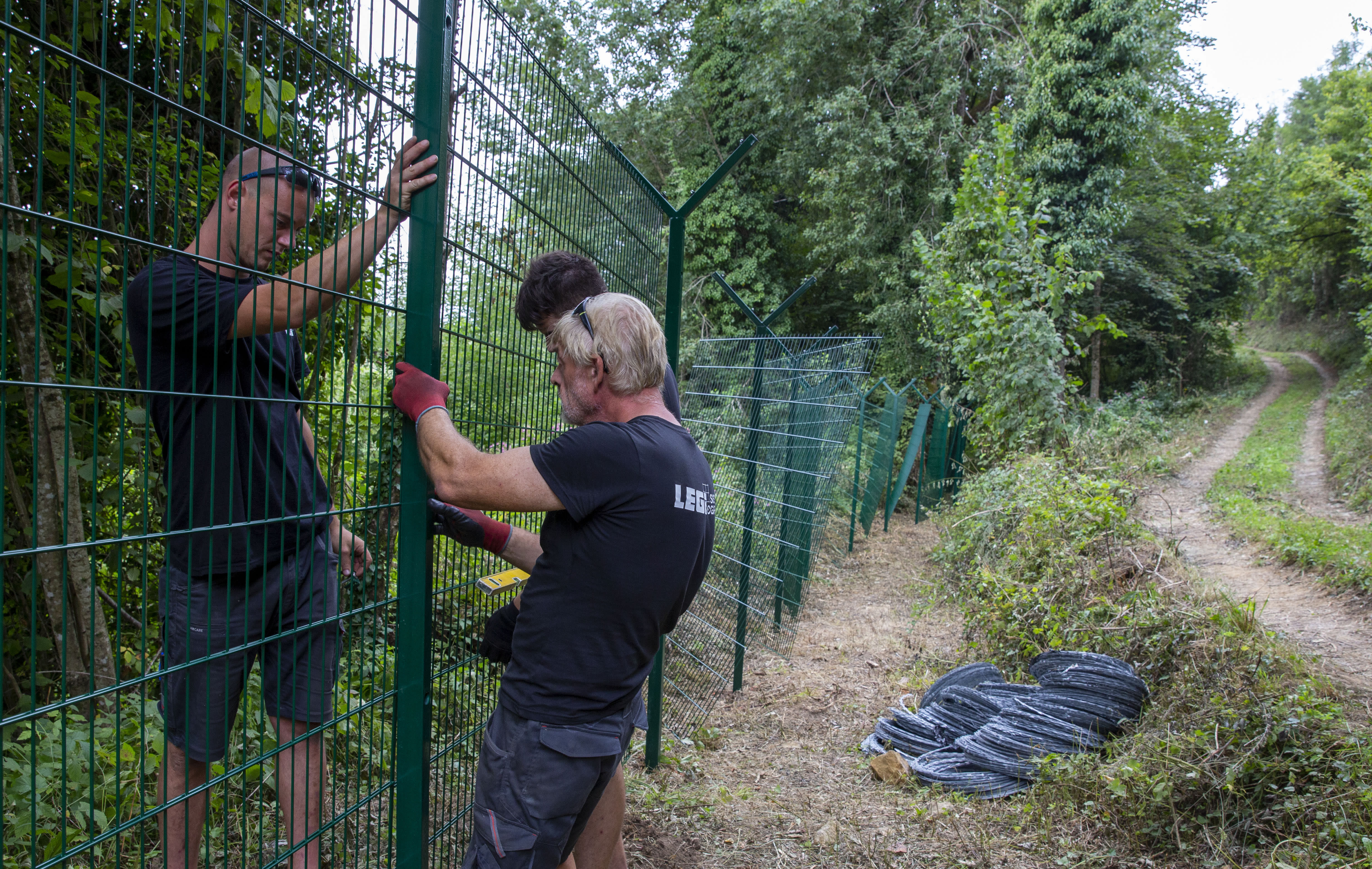 In this photo taken Friday, Aug. 23, workers put up a border fence next to the Kupa river on the Slovenia-Croatia border in the village of Preloka, Slovenia. Police in Croatia say a migrant has died after a van carrying 12 of them plunged into a river near the border with Slovenia, early Sunday. Slovenia started erecting additional fences on its southern border with Croatia after a considerable increase in the number of migrants trying to illegally cross between the two European Union-member states. (AP Photo/Darko Bandic)